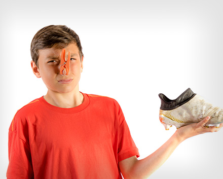 A Boy Holding a Smelly Sports Sneaker