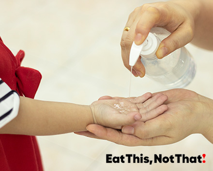 Image of a woman putting hand sanitizer in a childs hand